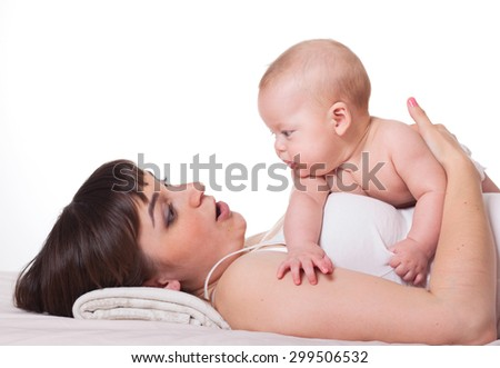 Cute happy family mother and baby on white background, mum talking to kid, child lying on mom