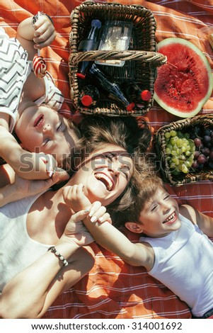 cute happy family on picnic laying on green grass mother and kids, warm summer vacations close up - stock photo
