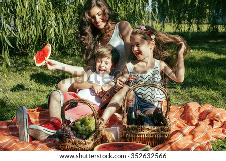 cute happy family on picnic laying on green grass mother and kids, warm summer vacations close up hot - stock photo