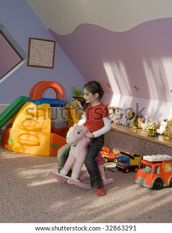 cute happy girl child plays toys rocking-horse in game room at school - stock photo