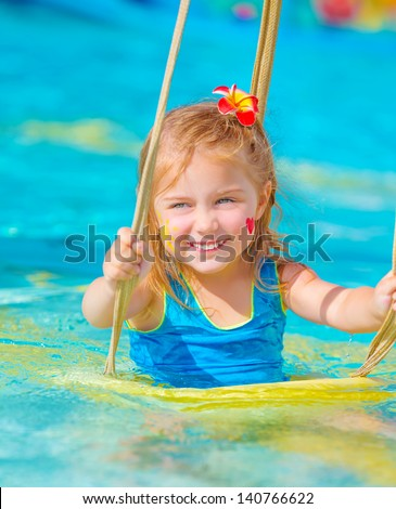 Cute happy girl enjoying summer holiday in the pool, having fun on water swing, red frangipani flower in hair, red heart print and yellow sun print on cheeks - stock photo