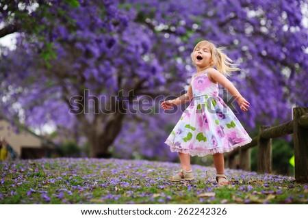 Cute happy girl has a fun, singing and dancing in a blooming jacaranda garden - stock photo