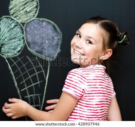 Cute happy girl is eating ice-cream. On a black background - stock photo