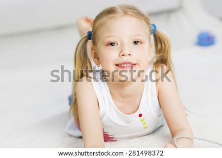 Cute happy girl lying on floor and dreaming - stock photo