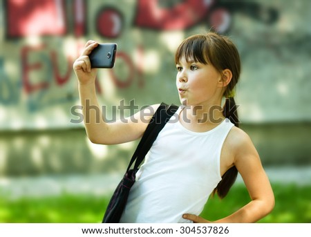 Cute happy girl makes self-portrait on the smartphone - stock photo