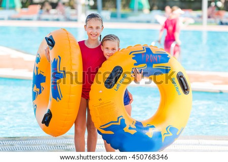 Cute happy girls in amusement aqua park. Summertime, vacation concept.