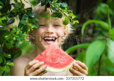 Cute happy kid eating watermelon in summertime in the garden - stock photo