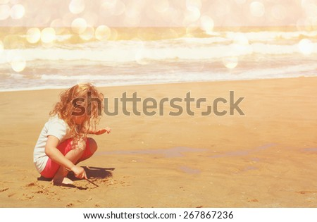 cute happy kid (girl) playing at the beach. toned image with glitter overlay  - stock photo