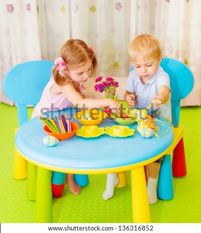 Cute happy kids make painted eggs at school, traditional Easter symbol, art lesson, best friends drawing on classroom - stock photo