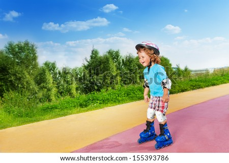 Cute happy laughing thee years little old boy rollerblading skating downhill in the park on sunny summer day - stock photo