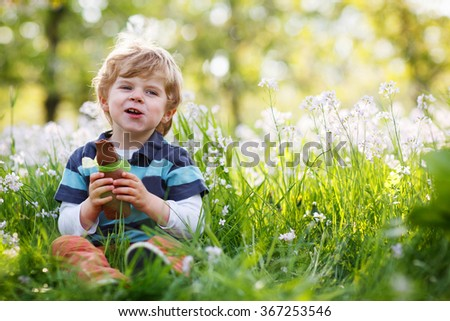 Cute happy little boy eating chocolate bunny and having fun outdoors at Easter holiday.