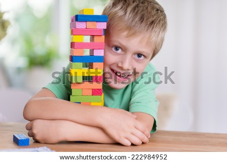 Cute happy little boy hugging a colorful tower on the dining table that he has just built from building blocks peering around the side at the camera with a cheeky grin - stock photo