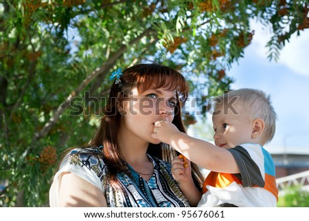 cute happy little boy lifting by his mother picking ashberry
