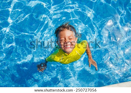 Cute happy little boy swimming and snorking in the swimming pool