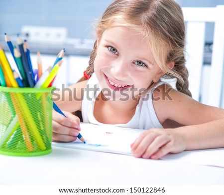 cute happy little girl drawing with pencils at home in the album