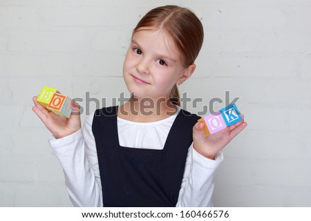 Cute happy little girl in school uniform plays with children's cubes with letters/Young schoolgirl puts the words of children's blocks - stock photo