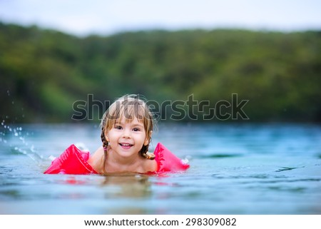 cute happy little girl learning swim at the ocean with floatation device - stock photo