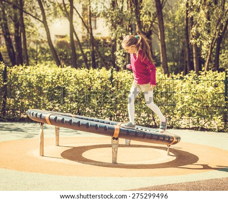 cute happy little girl on outdoor playground - stock photo