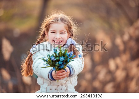 cute happy little girl smiling and holding a bouquet of blue  snowdrops - stock photo