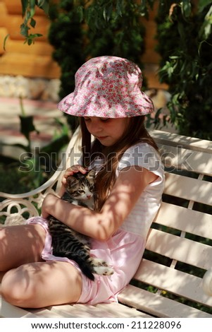 Cute happy little girl with a kitten sitting on a wooden bench in the sunny summer garden outdoor on a healthy holiday - stock photo