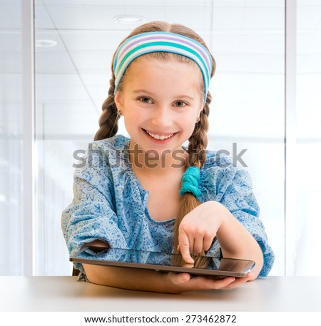 Cute happy little girl with her tablet - stock photo