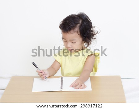 cute happy little girl writing something in her notebook - stock photo