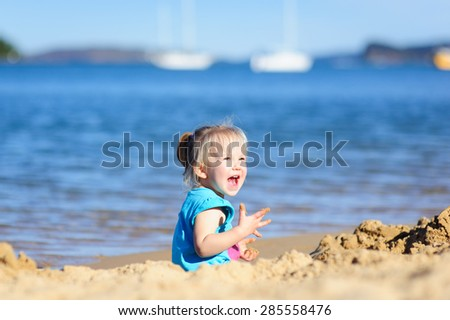 Cute happy little toddler girl playing with the sand at the beach on a sunny summer day