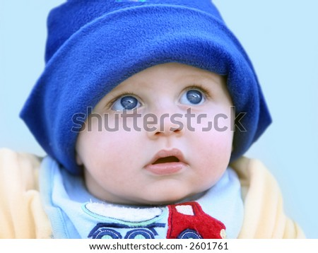 Cute happy 6 month old baby in a hat - stock photo