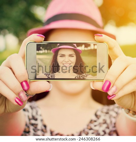 Cute happy redhead teenage girl with pink hat and nails taking a selfie with smartphone outdoors in park on sunny summer day. Square format, filter, saturated colors. - stock photo