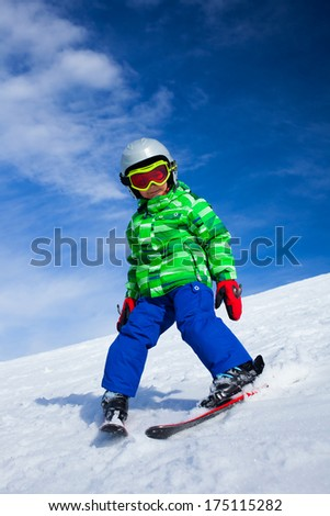 Cute happy skier boy in a winter ski resort. - stock photo