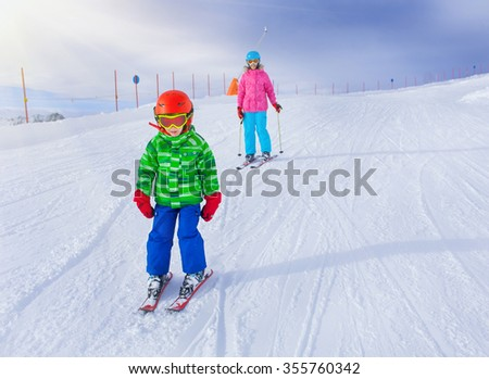 Cute happy skier boy on the sloap in a winter ski resort.
