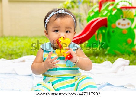 Cute happy smiling Asian baby playing toy.