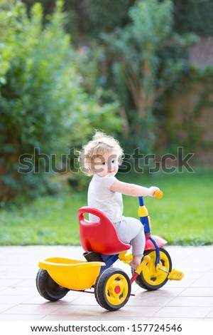 Cute happy smiling baby girl riding her first bicycle in the back yard of her house - stock photo