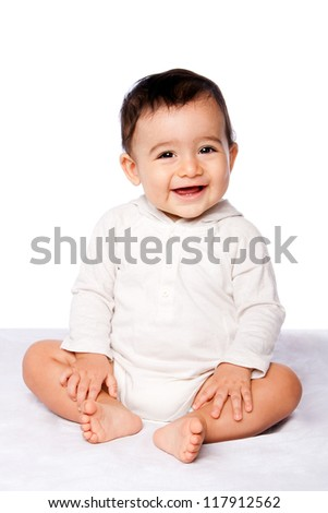 Cute happy smiling baby sitting on bed showing teeth, teething concept.