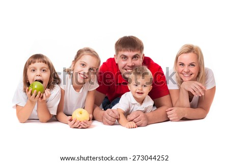 Cute happy smiling family of two sisters daughters with parents and junior brother posing with fruit apples - stock photo