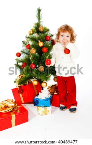 Cute happy toddler beside the Christmas tree with gifts under it - stock photo