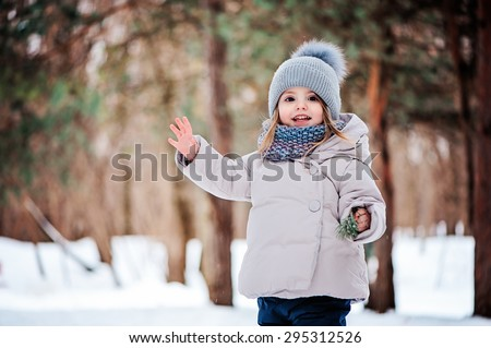 cute happy toddler girl playing with snow in winter park - stock photo
