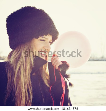 Cute happy young Caucasian blonde teenage girl holding red balloon wearing black fur hat looking sideways posing outdoors in winter. Happiness and teenage lifestyle concept. - stock photo