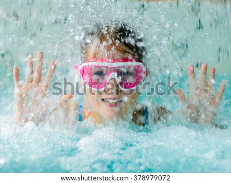 Cute happy young girl child playing in swimming pool under  a cascade of water - wearing pink goggles mask - stock photo