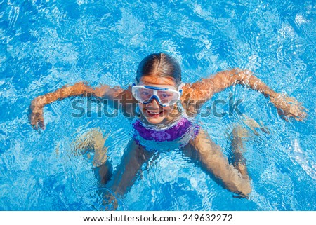 Cute happy young girl in goggles swimming and snorking in the swimming pool - stock photo