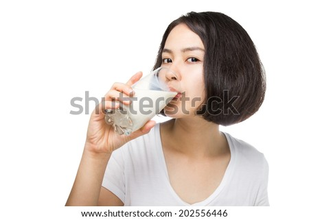Cute healthy woman is drinking milk from a glass isolated on white background.  - stock photo