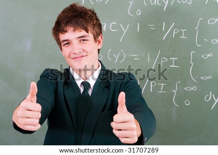 cute high school student in front of blackboard in classroom - stock photo