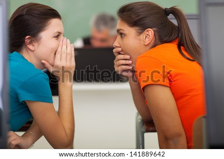 cute high school students gossiping in classroom - stock photo