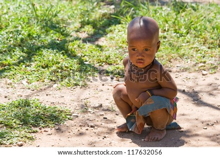 Cute Himba boy sitting in shade and looking away. - stock photo