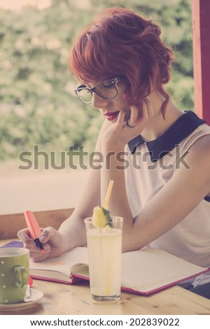 Cute hipster teenage girl daydreaming in a coffee shop, drawing hearts in her notebook,  - stock photo