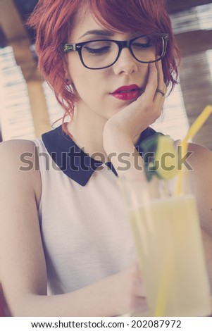 Cute hipster teenage girl in a coffee shop, daydreaming, enjoying lemonade. Retro styled imagery, toned image - stock photo