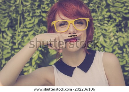 Cute hipster teenage girl with mustache hand drawn on  a finger she placed over her lips, cute and funny. Retro colors
