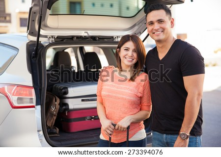 Cute Hispanic couple loading luggage to a car before going on a road trip - stock photo