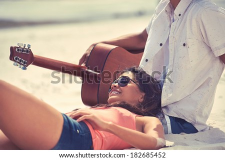 Cute hispanic couple playing guitar serenading on beach in love and embrace - stock photo