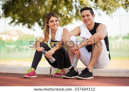 Cute Hispanic couple relaxing and drinking water after working out together at a running track outdoors - stock photo